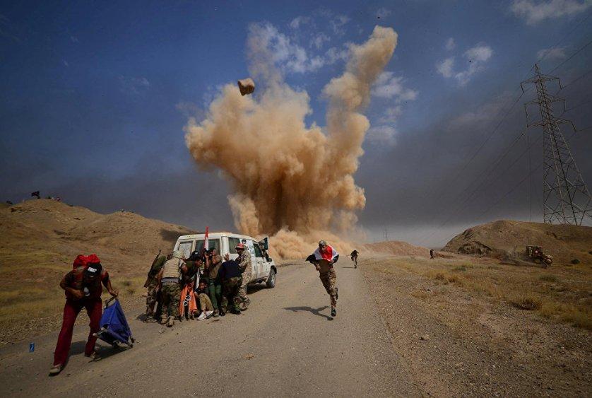 Шиитские народные мобилизационные силы укрываются от взрыва неподалеку от города Хавия, Ирак.