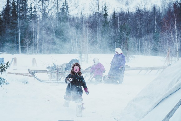 a Nenets boy plays outside in a snowstorm