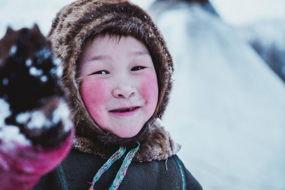 a nenets boy plays in the snow during Russian Arctic Travel's winter Nenets trip