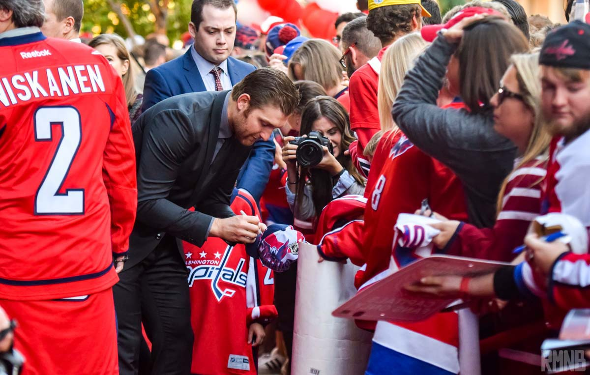 Karl Alzner signs an autograph for a tiny fan