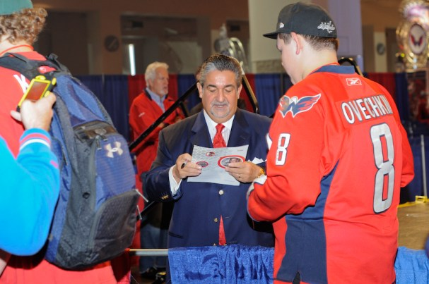 Caps Owner Ted Leonsis signs autographs for fans.