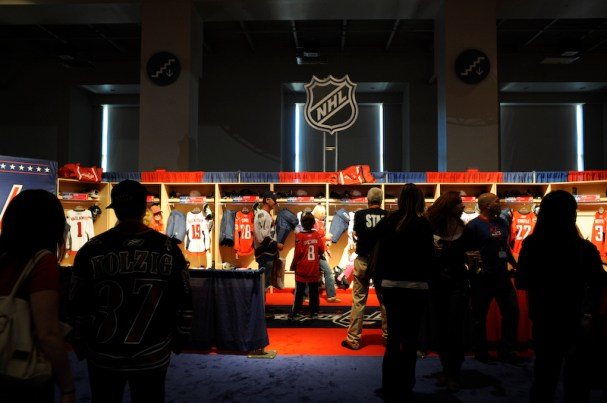 People look on, as a child looks at the Caps Convention's replica lockerroom area.