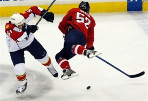 Mike Green tumbles to the ice after knee-to-knee hit. (Photos via AP)