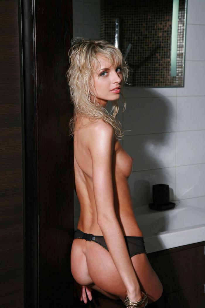 Skinny but busty blonde posing in bath in stockings