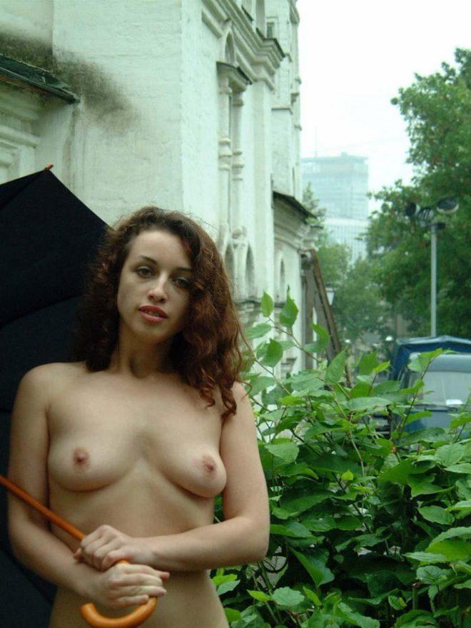 Curly damsel in a church garden rainy day