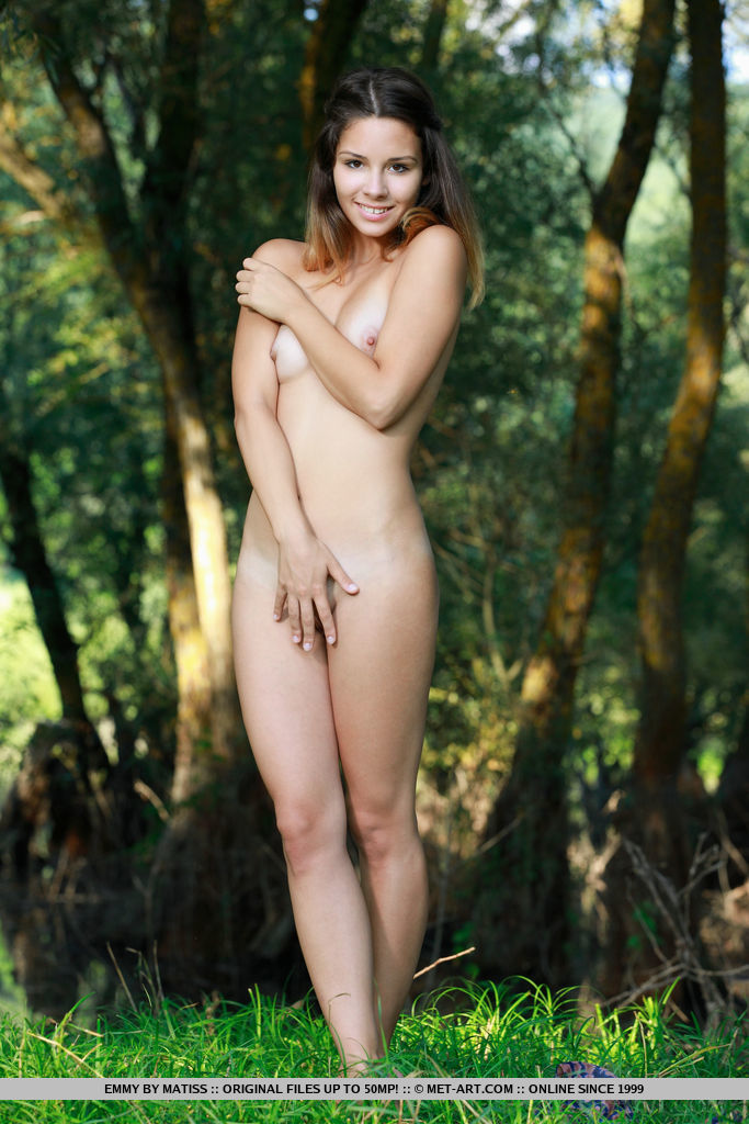 Emmy delightfully posesin the forest as she shows off her nubile body.