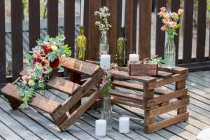 Repurposed pallets with candles and flowers on arranged on a deck