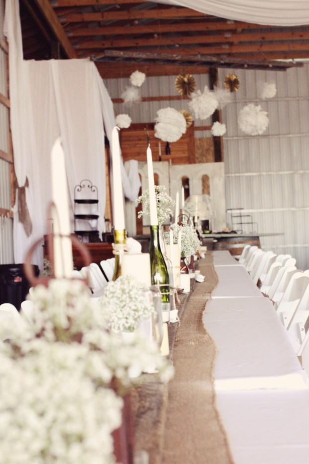 Tables lined in burlap, barnwood, candles, lanterns and baby's breath