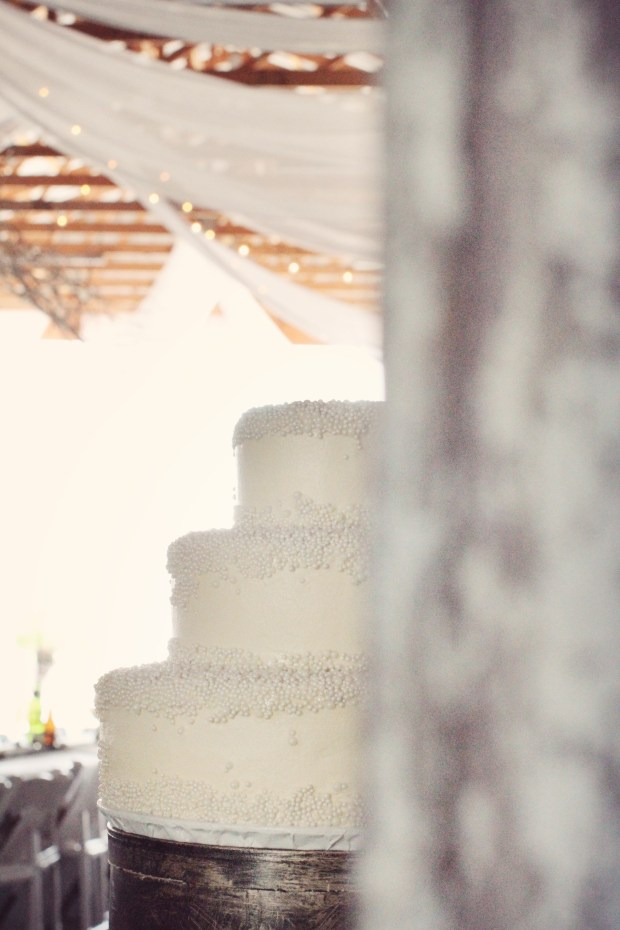 Three tiered wedding cake dripping with edible pearls