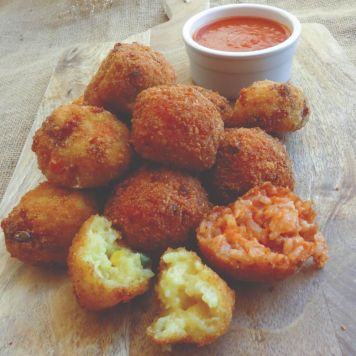 You are looking at a small pile of arancini balls with a saucer of sauce.