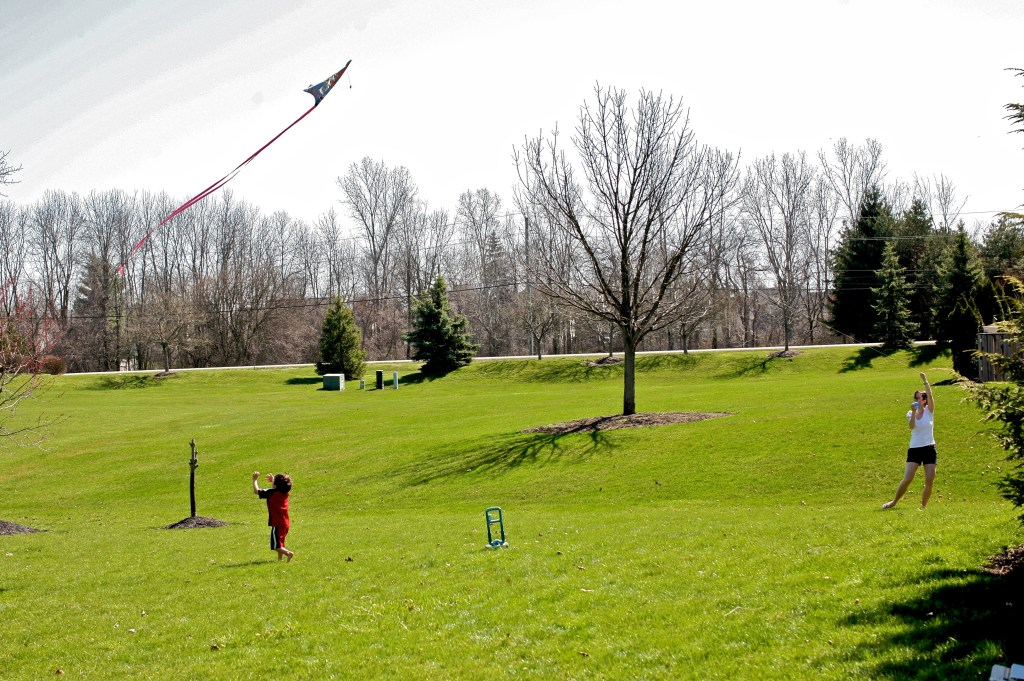 Michael and Laura fly a kite in the backyard,