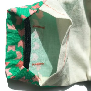 filter pocket of Green curved face mask with Pink tile accents