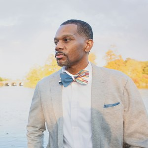man wearing blue/multi color stripe bow tie