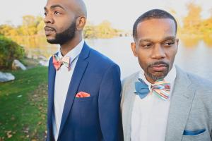 2 men with multi color striped bow tie in pink (left) and blue (right) variations