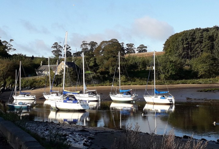 White picturesque sailing boats sitting in river Almond at low tide. Green trees lining the far away bank of the river with fields beyond. Old ferryman's house in the background. Pale blue sky with some fluffy clouds.