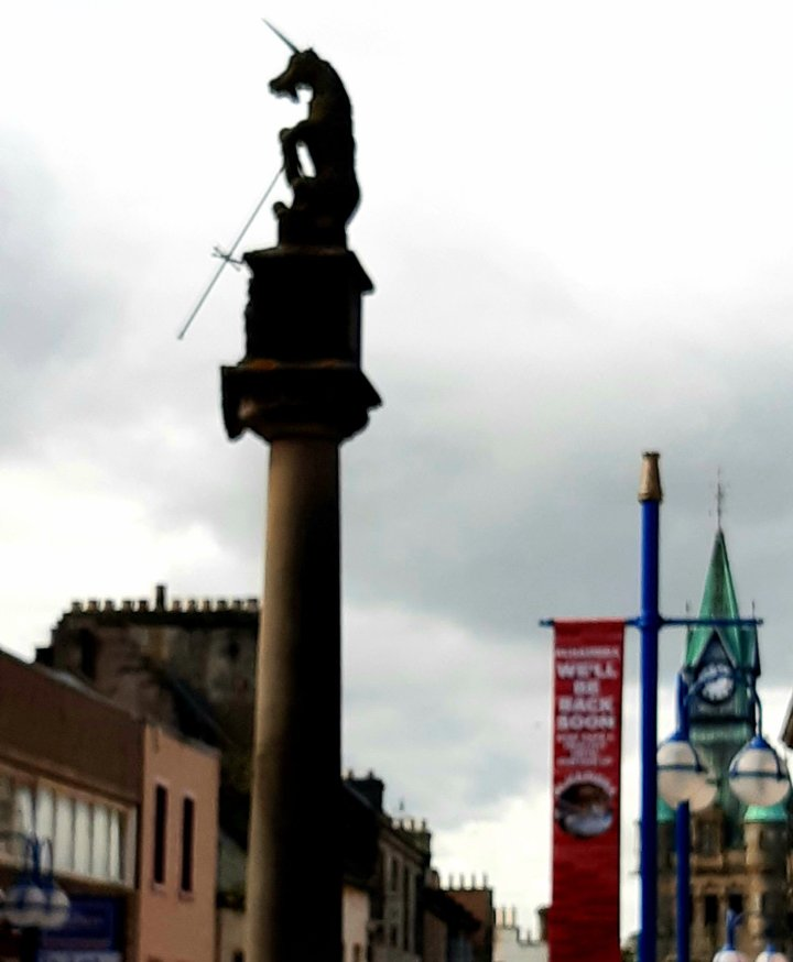 Looking up in Dunfermline High Street to Mercat Cross, symbol of trade in the old days. Behind it on the left uppermost floor and roofs of buildings, the first one pink other ones sandstone with multiple chimneys each. On the right behind the crossfire back the old city chambers with a green roof and turrets. Between Mercat Cross and chambers a blue flagpole with a long narrow hanging banner in red. It advertises we will be back soon. The Mercat Cross itself is a sandstone narrow high pillar with a unicorn on top of it.