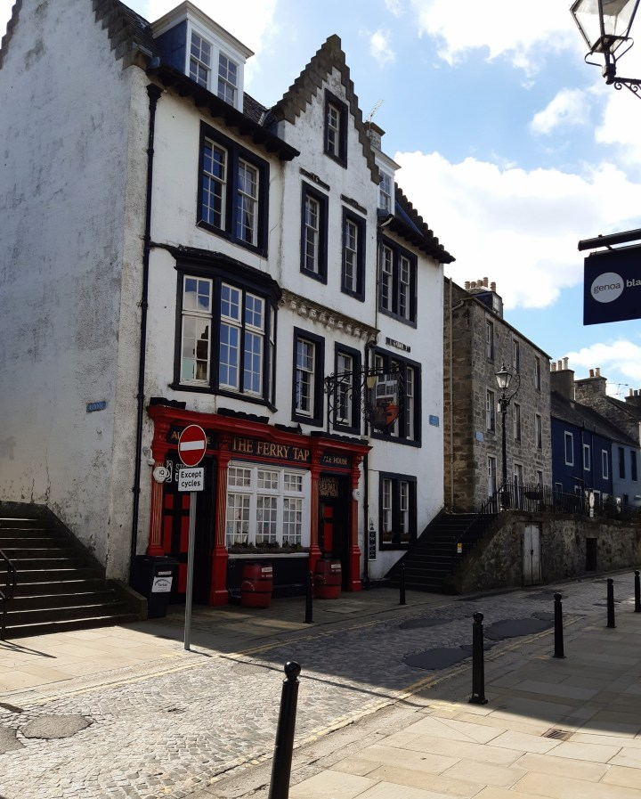 South Queensferry High Street, narrow street with no traffic. on the left steps next to a white 3 storey building. Front street level painted in red with large white framed window. All other windows have black frames and are very high. Crow stepped gable. Gable windows in the roof, the middle one with crow step decorative. The pub is at start of terrace of houses in various building materials and colour.