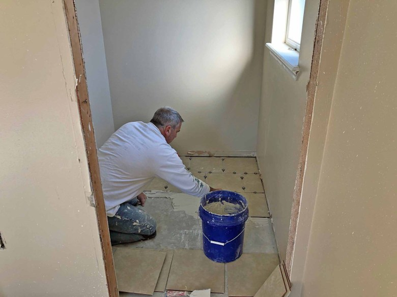 Brad Saum laying floor tile in a bathroom for a Habitat for Humanity build