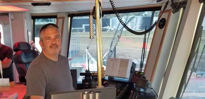 Brad Saum at the helm with the  Captain's view from the William James tug boat while docked in the Yazoo River.