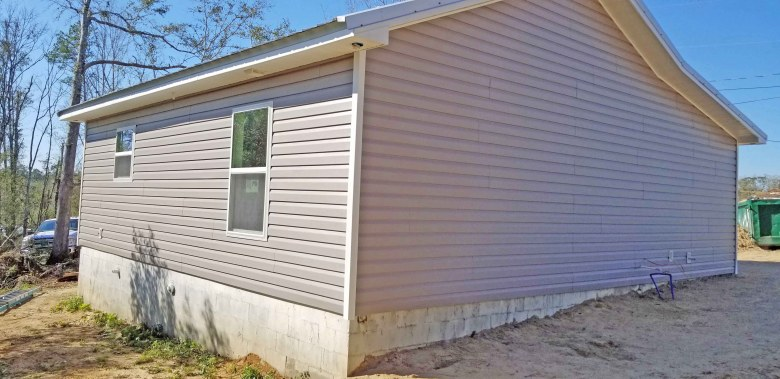Habitat for Humanity RV Care-A-Vanners install vinyl siding