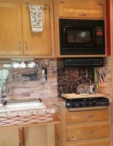 RV kitchen with stone wallpaper backsplash
