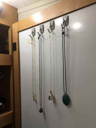 Command hooks on the back of an RV bathroom mirror make a handy place to hang necklaces.