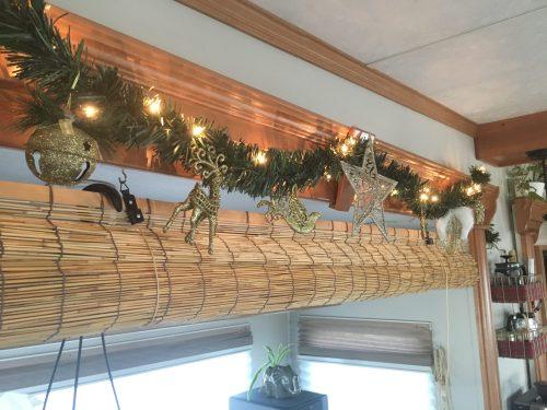 Lighted greenery hung across an RV slide as Christmas decor