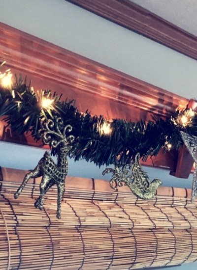 Lighted greenery hung across an RV slide as Christmas decor