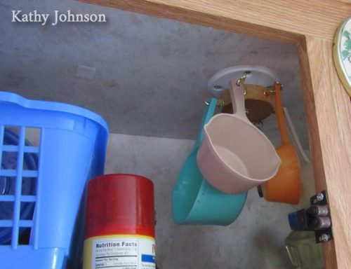 Mugs hung from hooks in the top of an #RV #kitchen cabinet