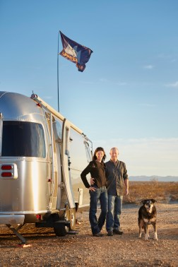 Brian Easterling and Leigh Wetzel stand outside their Airstream RV trailer while camping in the Anza Borrego desert of California.