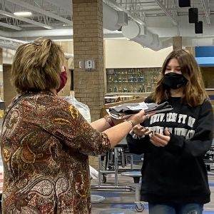 Principal hands items to student