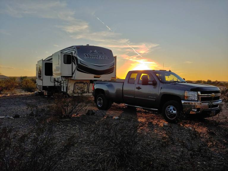 Truck full time RVing with sunset in the desert