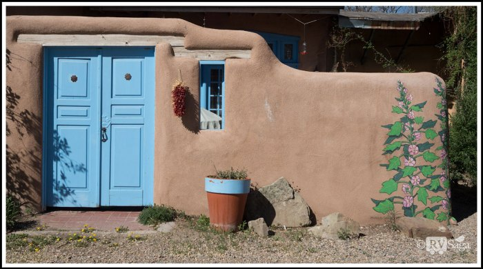 A-Blue-Door-on-An-Adobe-Wall-with-Painted-Flowers