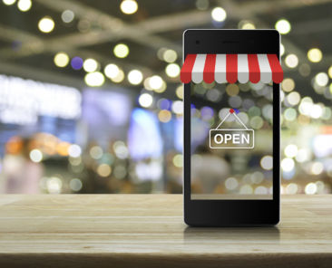 Modern smart mobile phone with on line shopping store graphic and open sign on wooden table over blur light and shadow of mall