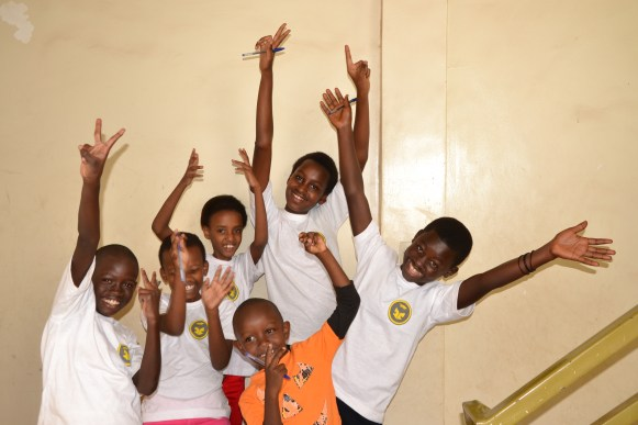 Children give their sponsors a thank you wave.