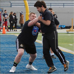 Windsor, ON April 17, 2016 -- Nicholas Tesolin (left) blocks a camp participant during the one-on-one portion of the 2016 Windsor's Finest Football Academy camp. Tesolin is a former high school football player from Holy Names who is attempting to continue his career at the colligate level. (Photo by Ryan Blevins)