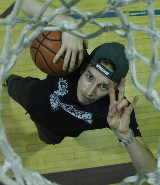 (Windsor, ON) -- Anthony Pollock poses for a portrait underneath the basket in the Catholic Central gym in Windsor on Tuesday, March 8, 2016. Pollock is a former high school basketball player and a voluenteer for this years AAA Boys Basketball OFSAA tournament. (Photo by Ryan Blevins)