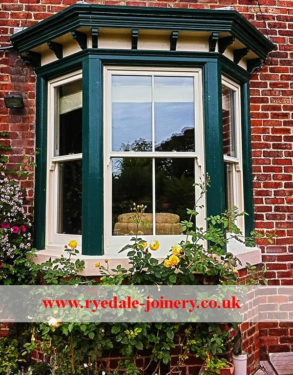 An image of a traditional sliding sash window that has been upgraded and double glazed. The window is painted green and cream and here are some really nice roses growing in the area immediately in front of the window.