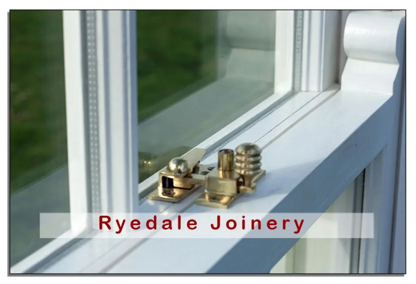 A close-up image of a new double-glazed sash window. The wood is painted white and the brass security locking mechanism is clearly in focus.  The window was manufactured by Ryedale joinery.