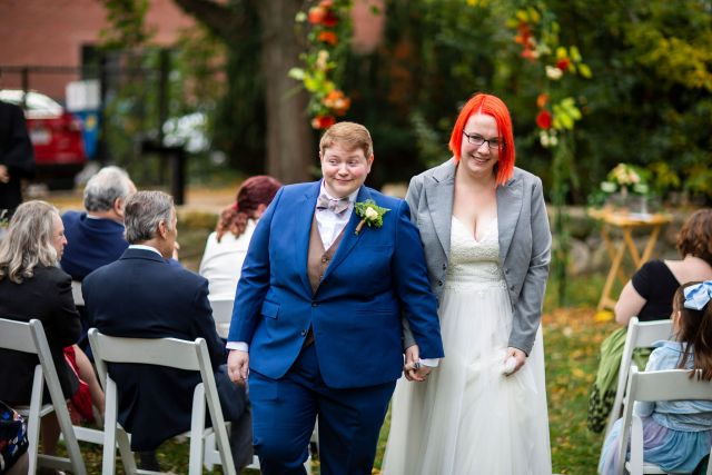 Mel & I walk hand-in-hand after the outdoor ceremony, smiling at family and friends.