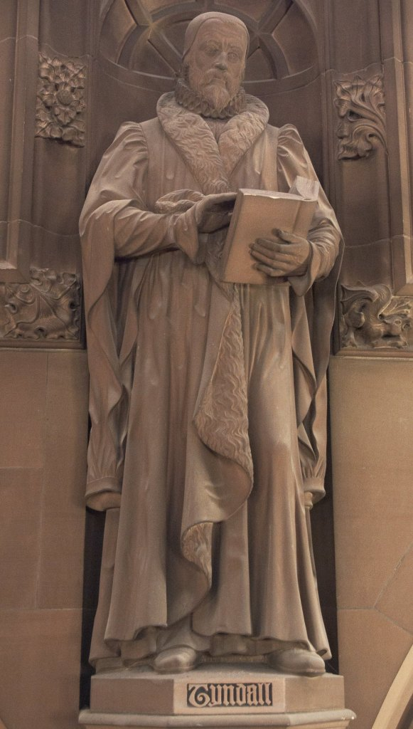 Stone statue of William Tyndale holding an open book