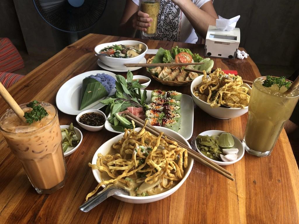 A spread of food from Aum Vegetarian Restaurant, Chiang Mai: khao soi, spring rolls, Thai milk tea, jasmine rice...