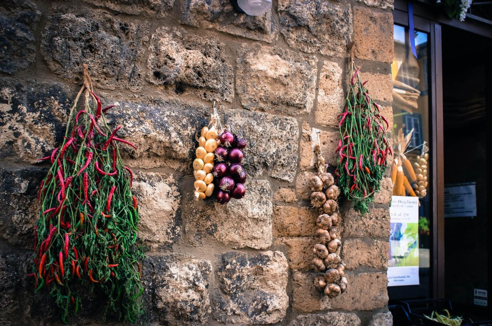 Italian herbs and spices hanging on stone wall