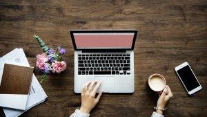 テーブルでパソコン右手にコーヒーを持ち、左手でパソコンに触れる画像