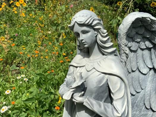 Statue d'ange avec un oiseau dans un jardin