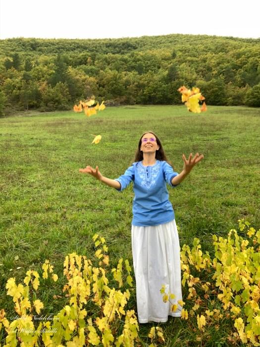 Jeune femme jetant en l'air des feuilles d'automne