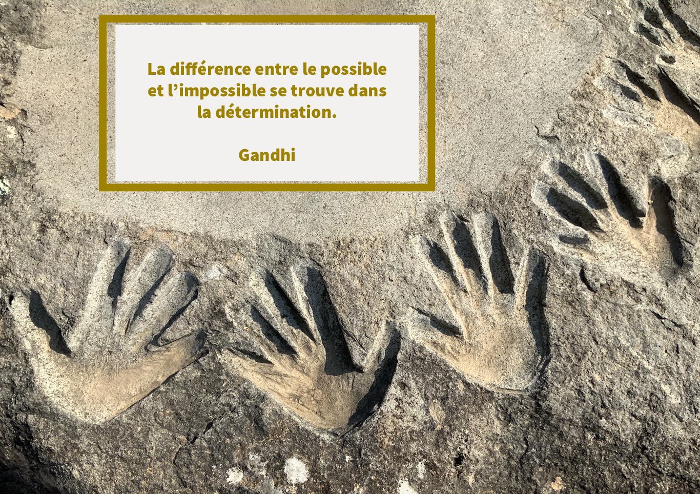 Citation de Gandhi sur une photo d'empreintes de main dans la pierre