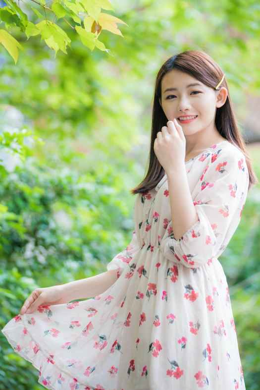 shallow focus photo of woman in white and pink floral long sleeved dress