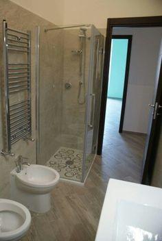 Bagno con doccia in mosaico sotto finestra