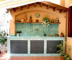 cucina in muratura con piastrelle in terracotta e top in pietra lavica con lavello in pietra